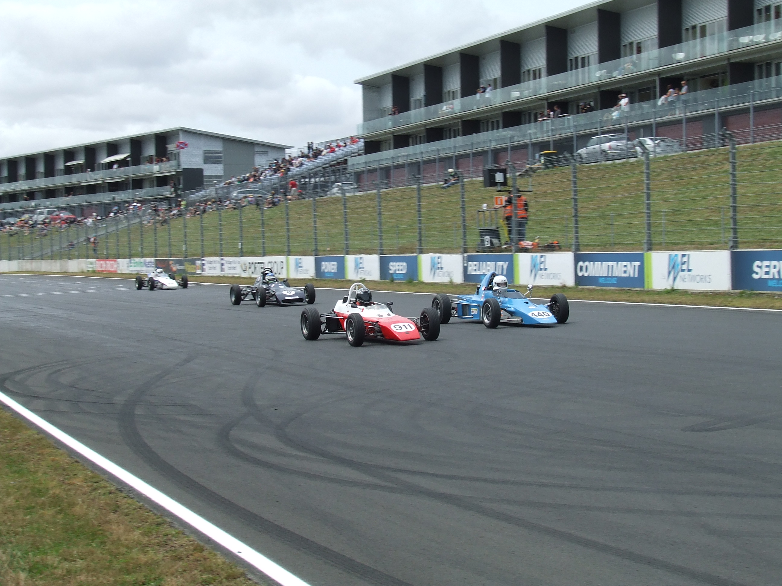 A gaggle of cars cross the start finish to start another lap